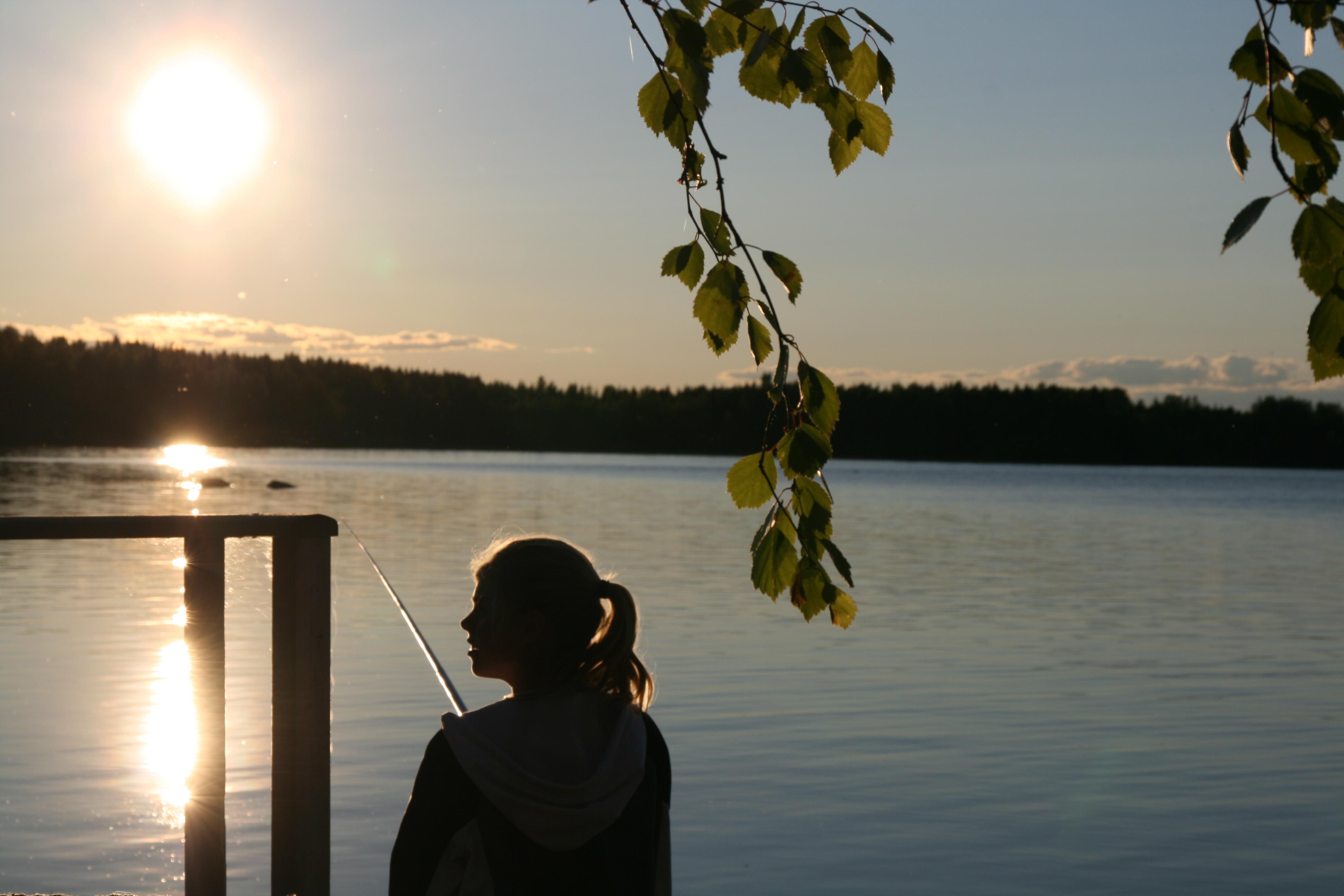 Tjej som fiskar i kvällssolen
