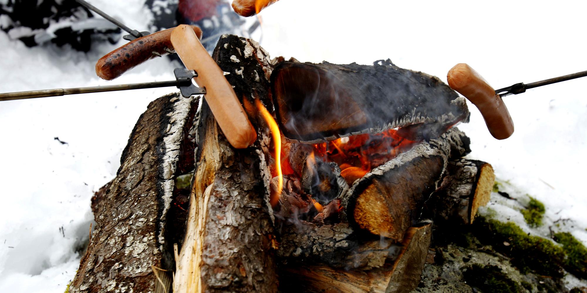Mokk gård - pølsegrilling over åpen flamme vinterstid. Copyright: Mokk gård