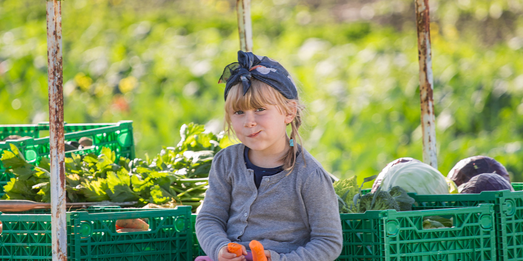Ystgård Garden Centre - girl enjoying delicious carrots grown at the garden centre. Copyright: Lena Johnsen