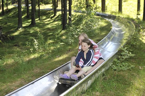 Två unga tjejer åker i full fart nedför Sommarrodel Kungsbygget