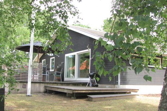 Hyr en modern välutrustad sommarstuga med stort trädäck och utemöbler av Mellbystrands Uthyrning