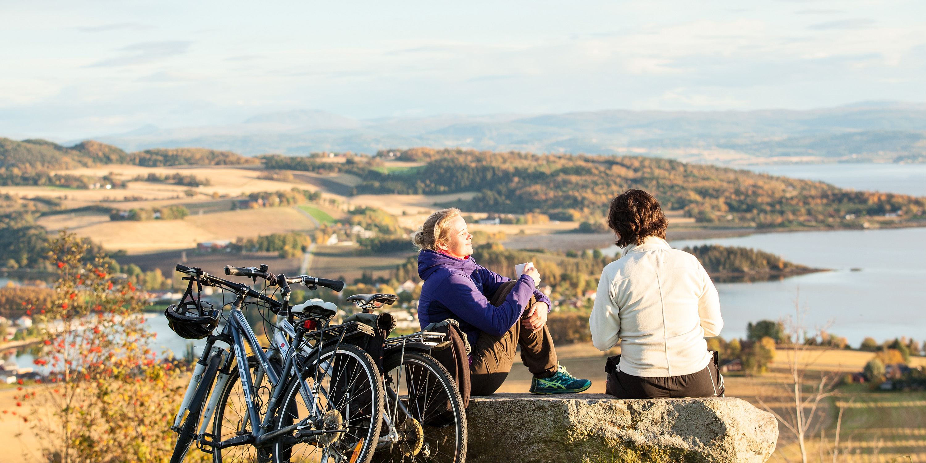 Cyclists taking a break and enjoying the panoramic view of the Trondheimfjorden at Øyna. Copyright: WilLee Wright