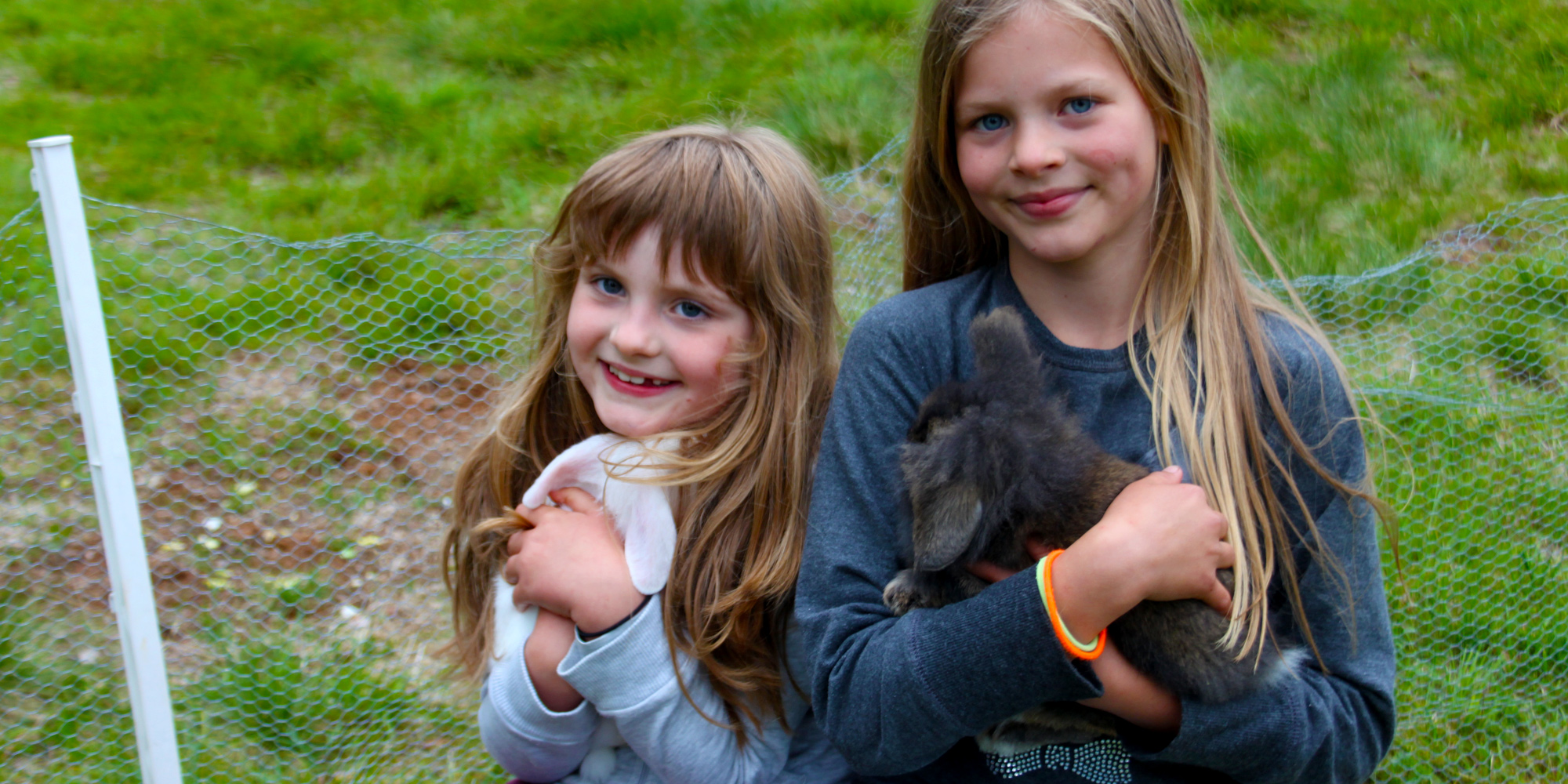 2 content girls petting the rabbits at Holsingsetern summer mountain farm. Copyright: Visit Innherred