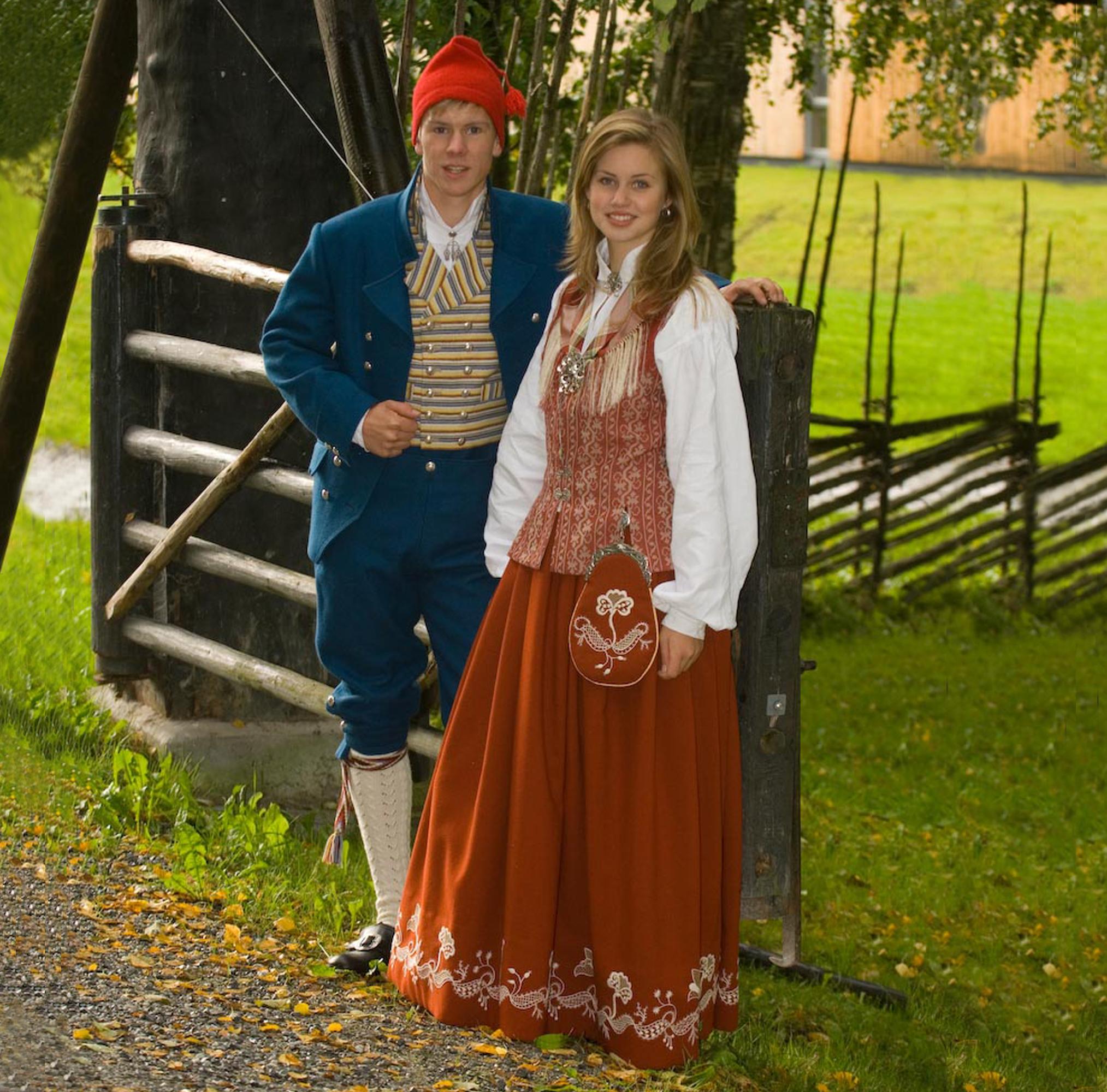 Floan/Nord-Trønderbunaden for dame og herre i Rustrød og kongeblå. Copyright: Bunadsaum